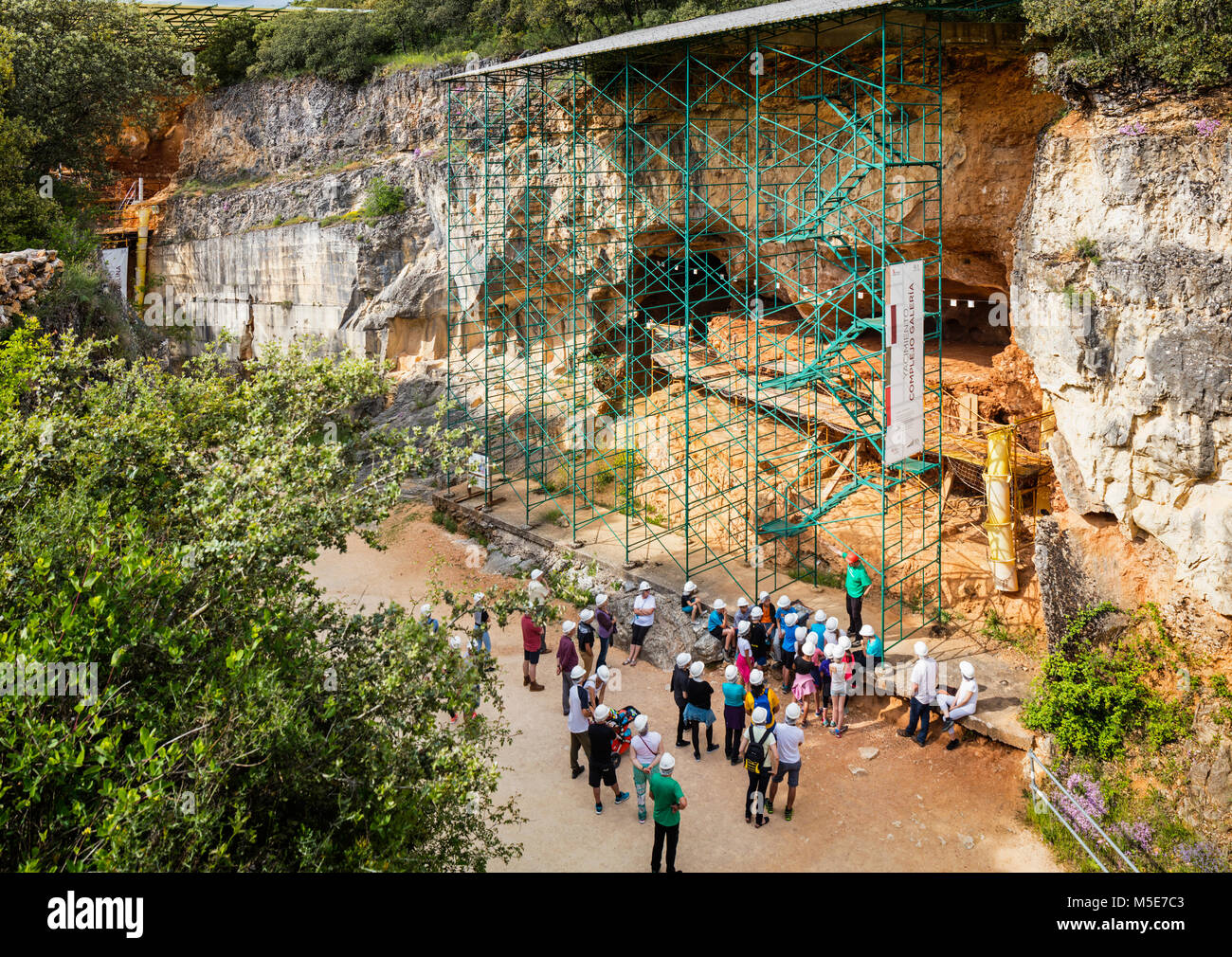 Visitors listening to an archeological guide at the Archeological site of Atapuerca, a UNESCO World Heritage Site - Stock Image