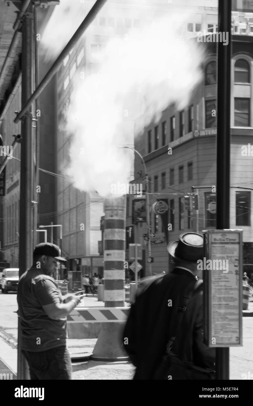New York, NY, USA - June 06, 2015:Steam coming out of Greeley Square and the intersection West 32 in Manhattan in - Stock Image
