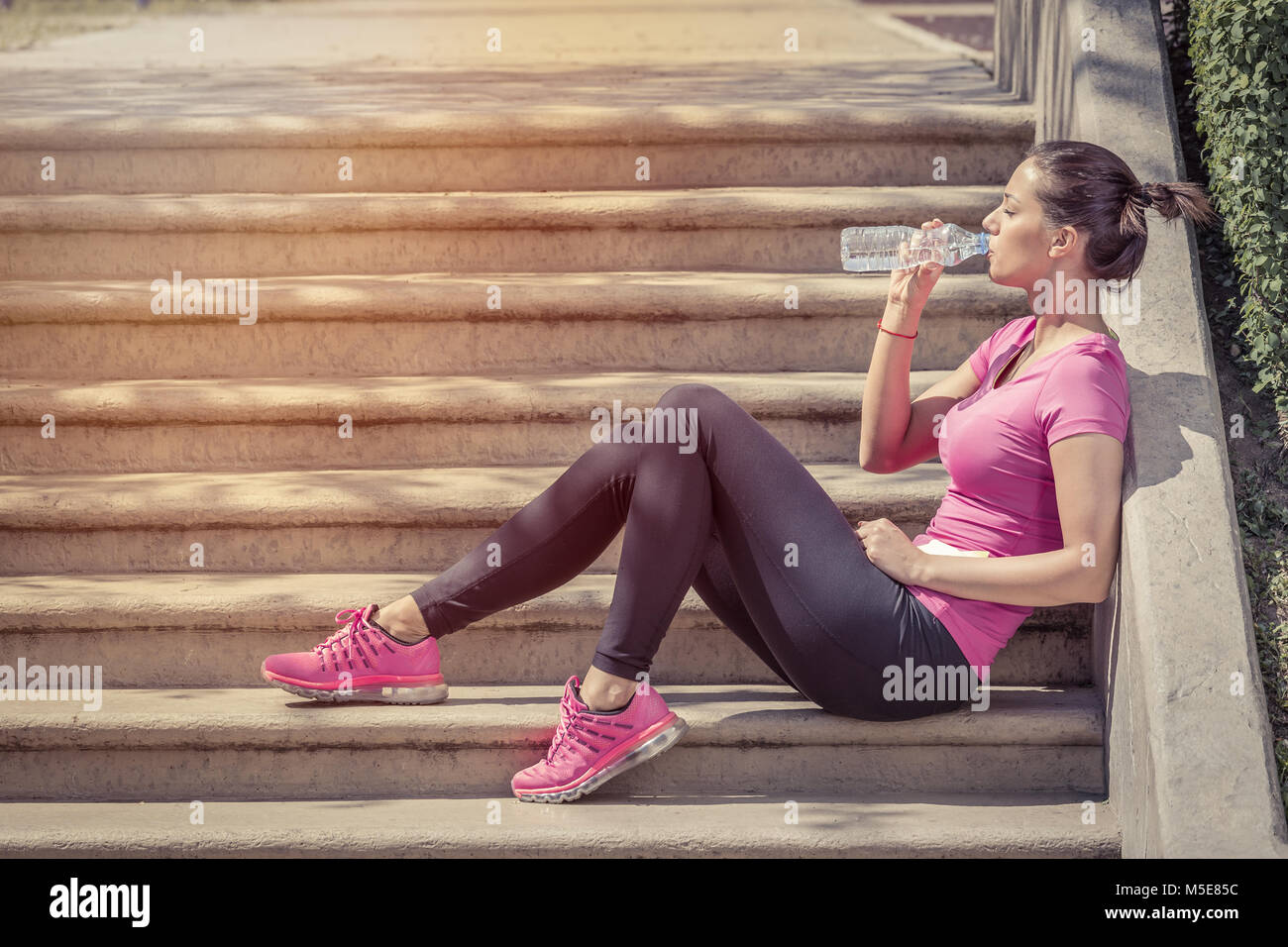 Fitness runner woman drinking water and sitting on staircase. Athlete girl taking a break during run to hydrate - Stock Image