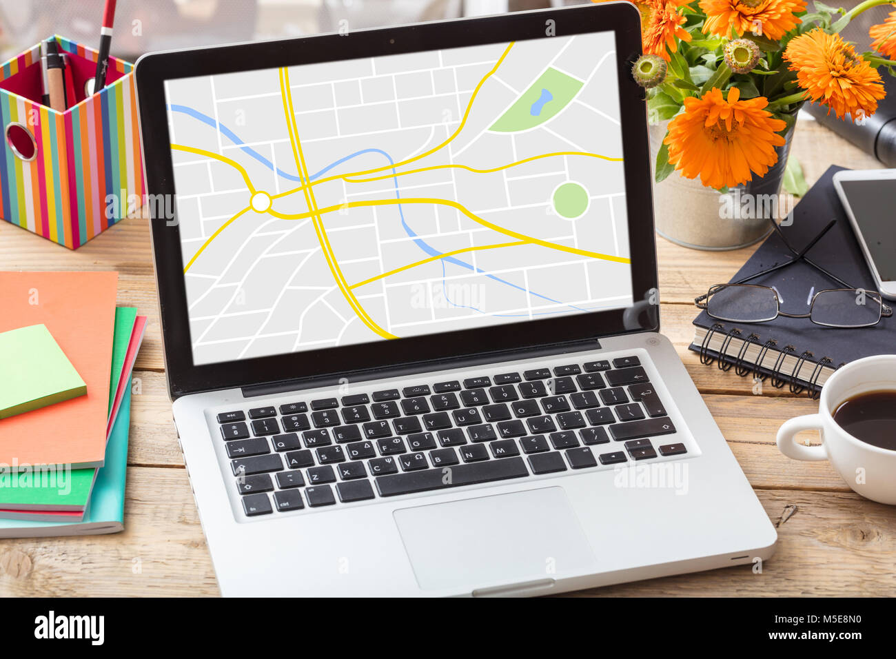 GPS, navigation. Map on a computer screen on a wooden office desk - Stock Image