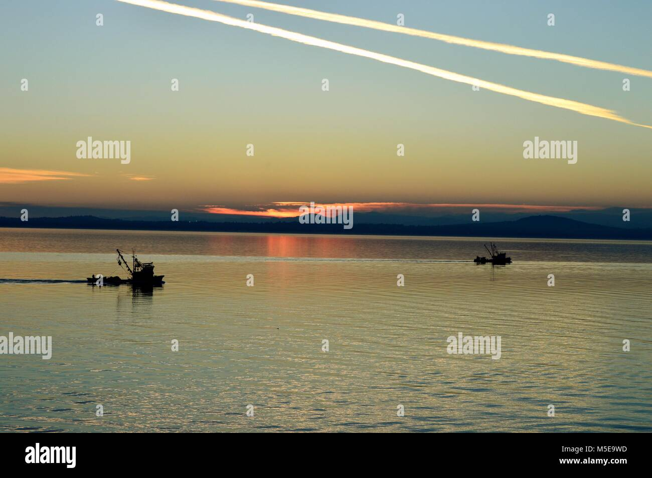 Two purse seiner fishing boats making their way home to Vancouver Island right after sunset - Stock Image