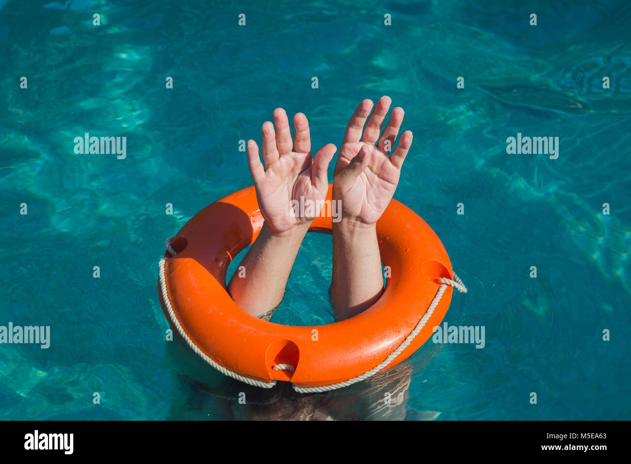 Close up of man hands through lifebelt in sea. Emergency drowning help concept - Stock Image