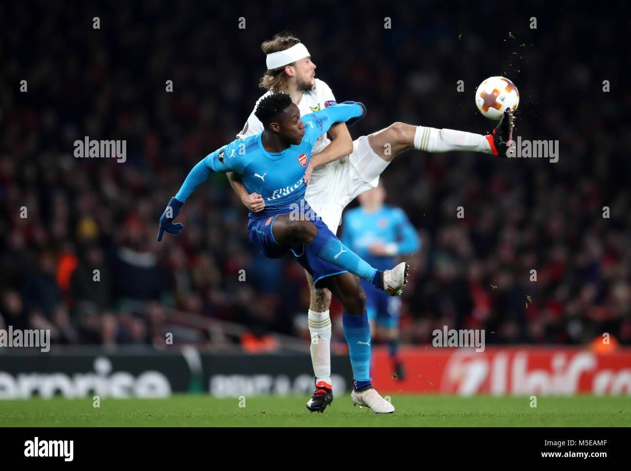 Ostersunds FK's Curtis Edwards and Arsenal's Danny Welbeck gestures on the touchline during the UEFA Europa League round of 32, second leg match at the Emirates Stadium, London. Stock Photo