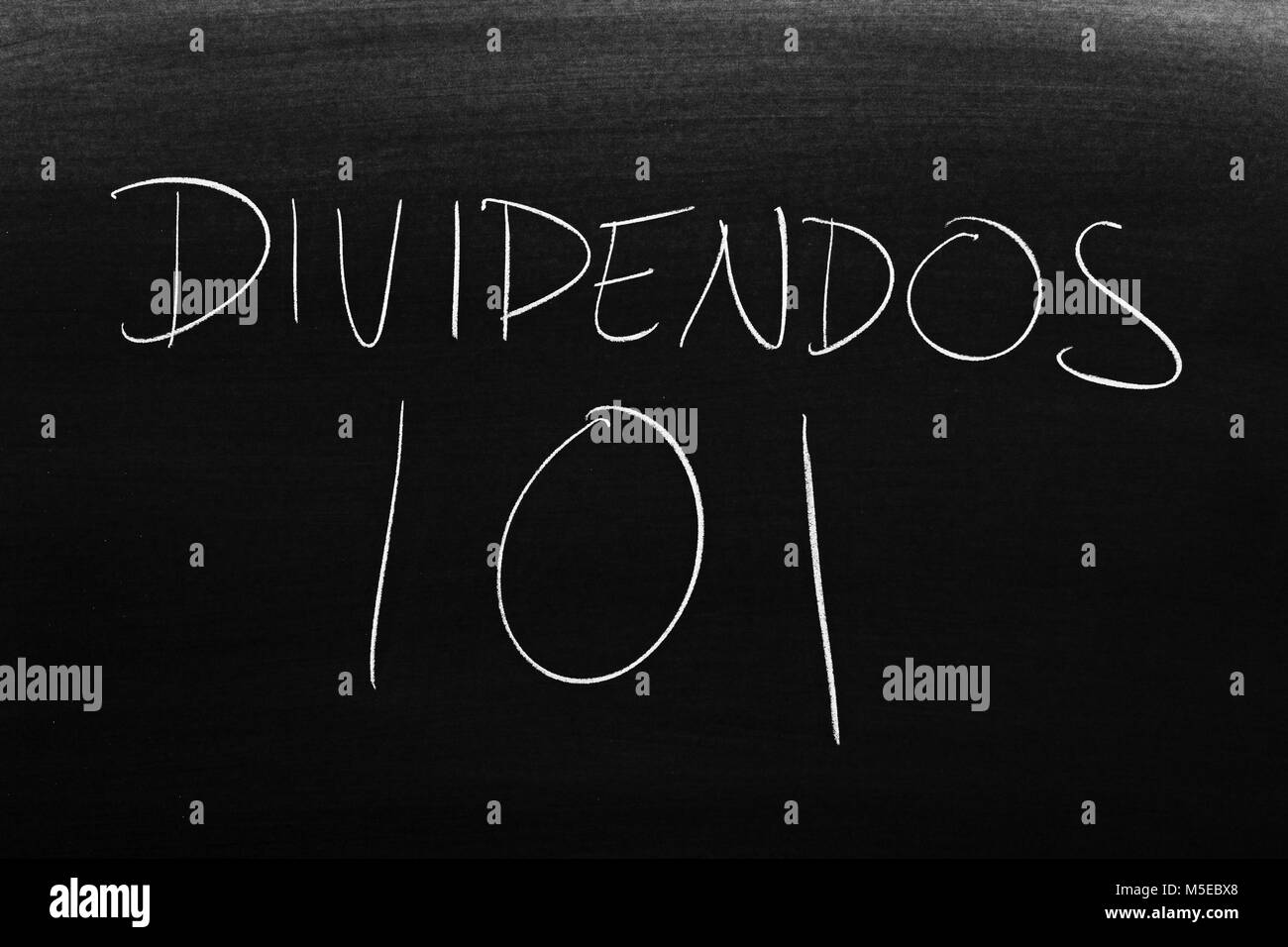 The words Dividendos 101 on a blackboard in chalk - Stock Image