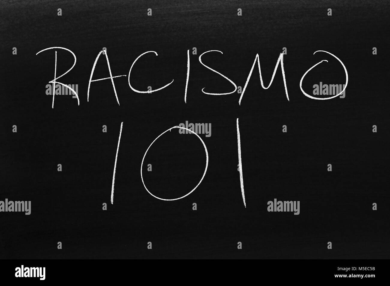 The words Racismo 101 on a blackboard in chalk - Stock Image