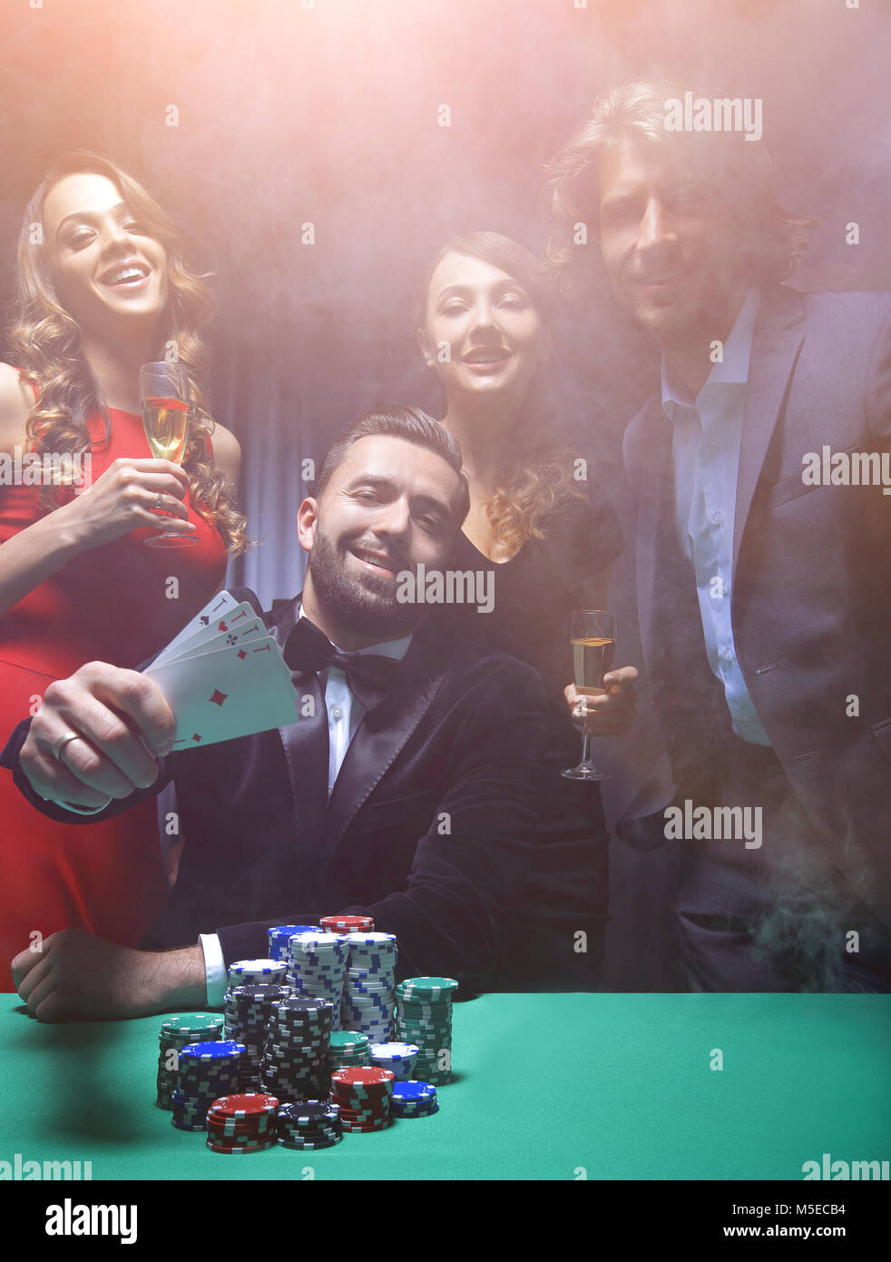 portrait of group of people with drinks playing poker in casino - Stock Image