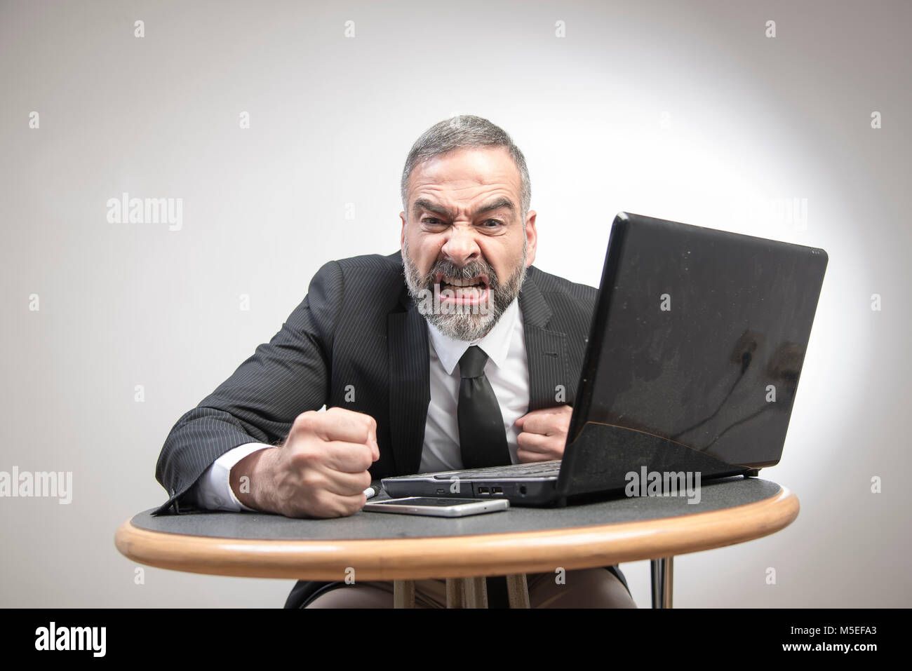 Senior business man shouting at his laptop, furious and frustrated with an email he receives - Stock Image