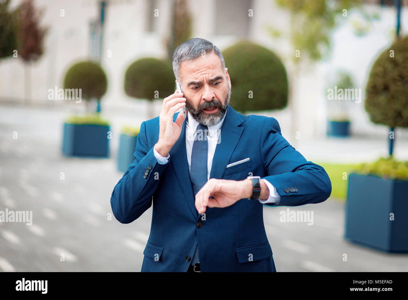 Senior mature business man shocked with the time, talking on his phone, expressing his fear - Stock Image