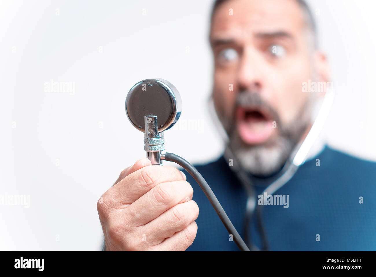 Senior man shocked and outraged with his blood pressure measurement result, studio image - Stock Image