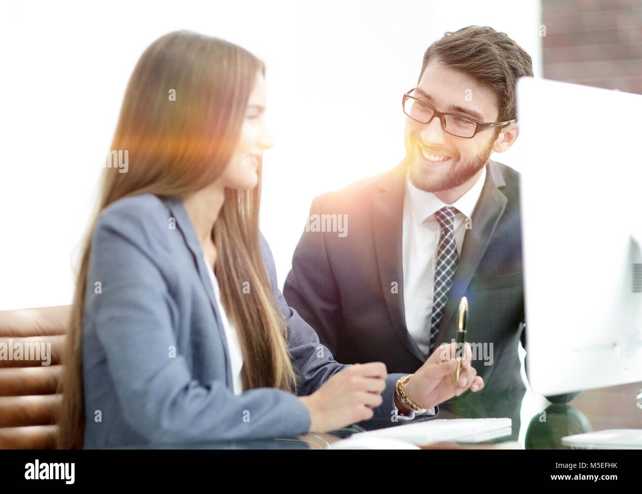 colleagues discussing information on a computer Stock Photo