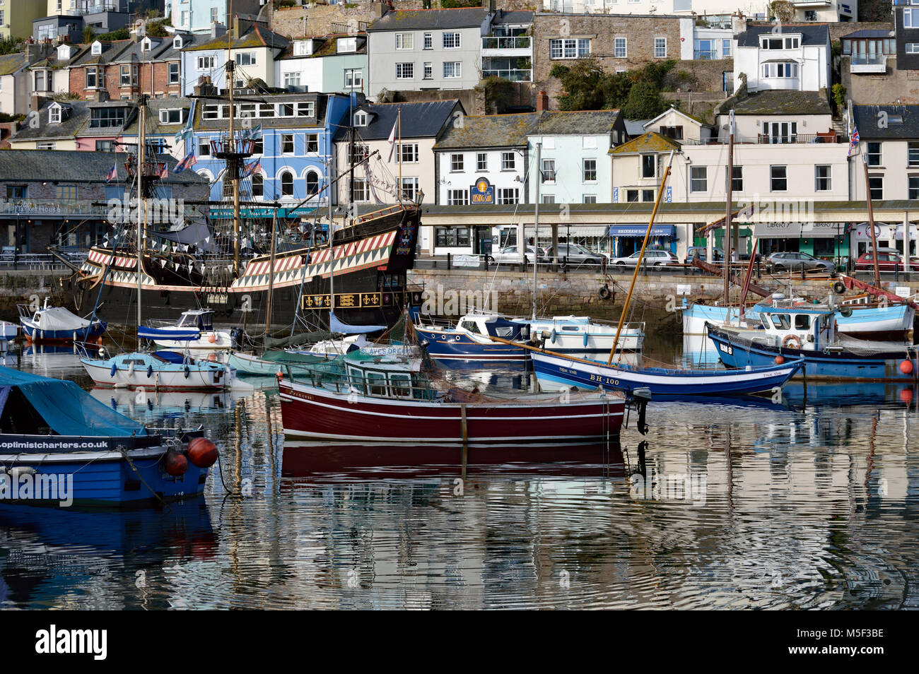 View of boats in Brixham Harbour including Golden Hind, Heritage Vessel 'IRIS' and True Vine with harbourside - Stock Image