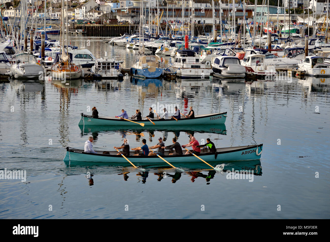 Brixham Gigs Trojan and Arion rowing out of Brixham harbour with yachts on the marina and fish quay in the background - Stock Image