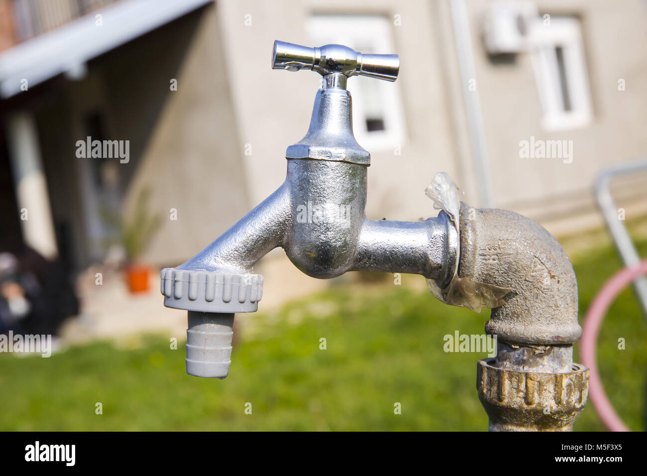 Wasting water - water drop from water tap - Stock Image