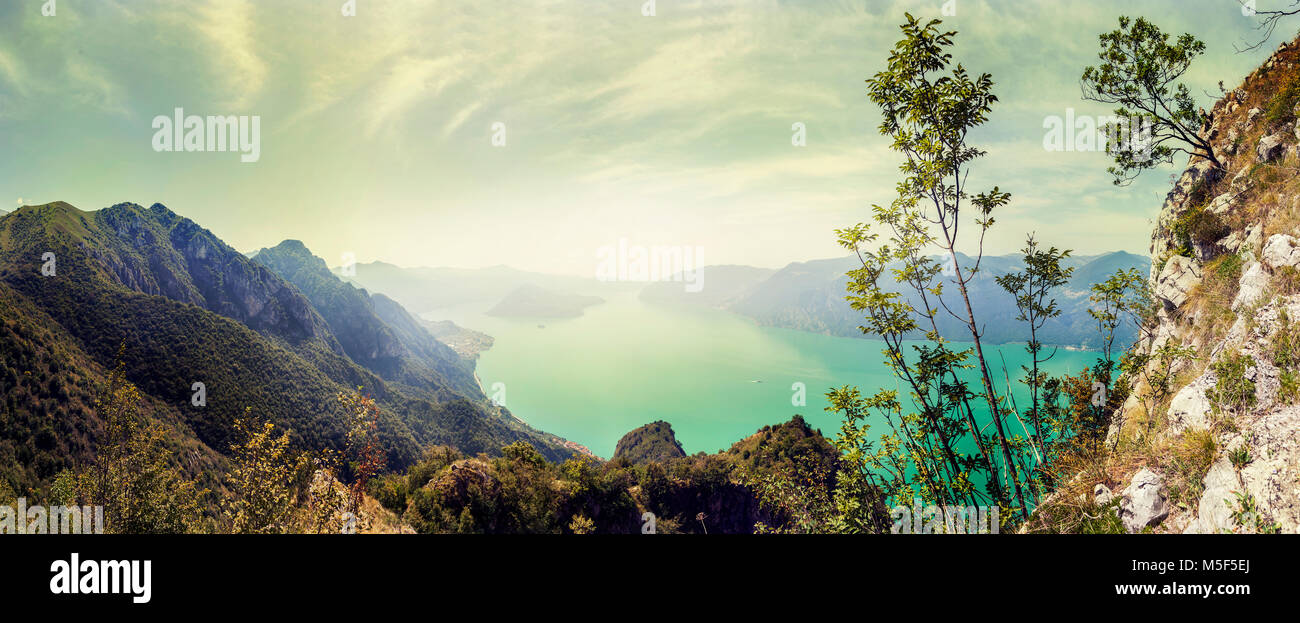 Panoramic aerial view of a mountain lake in a green valley. Famous Lake Iseo in the center of the Alps - Stock Image