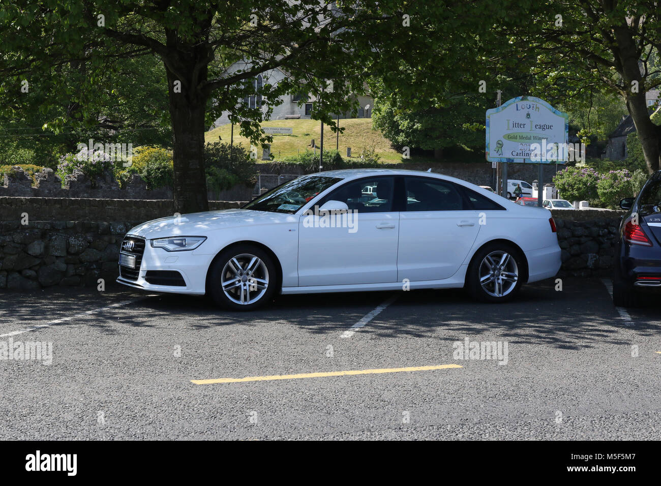 White Audi car badly parked across bays in car park. - Stock Image