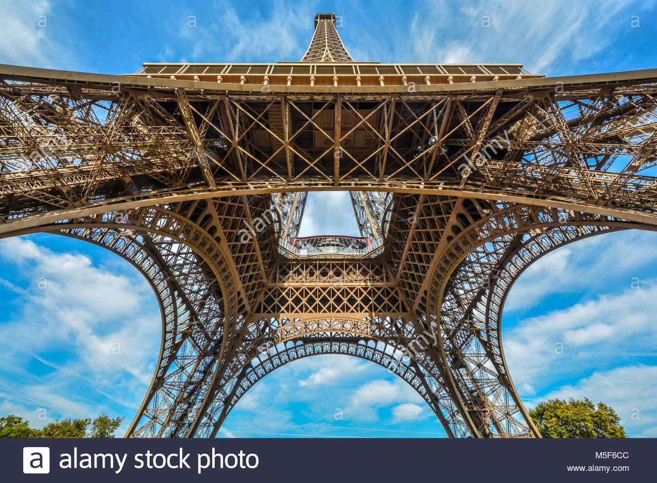 View looking up from underneath the Eiffel Tower on a sunny day with powder blue skies in Paris France - Stock Image
