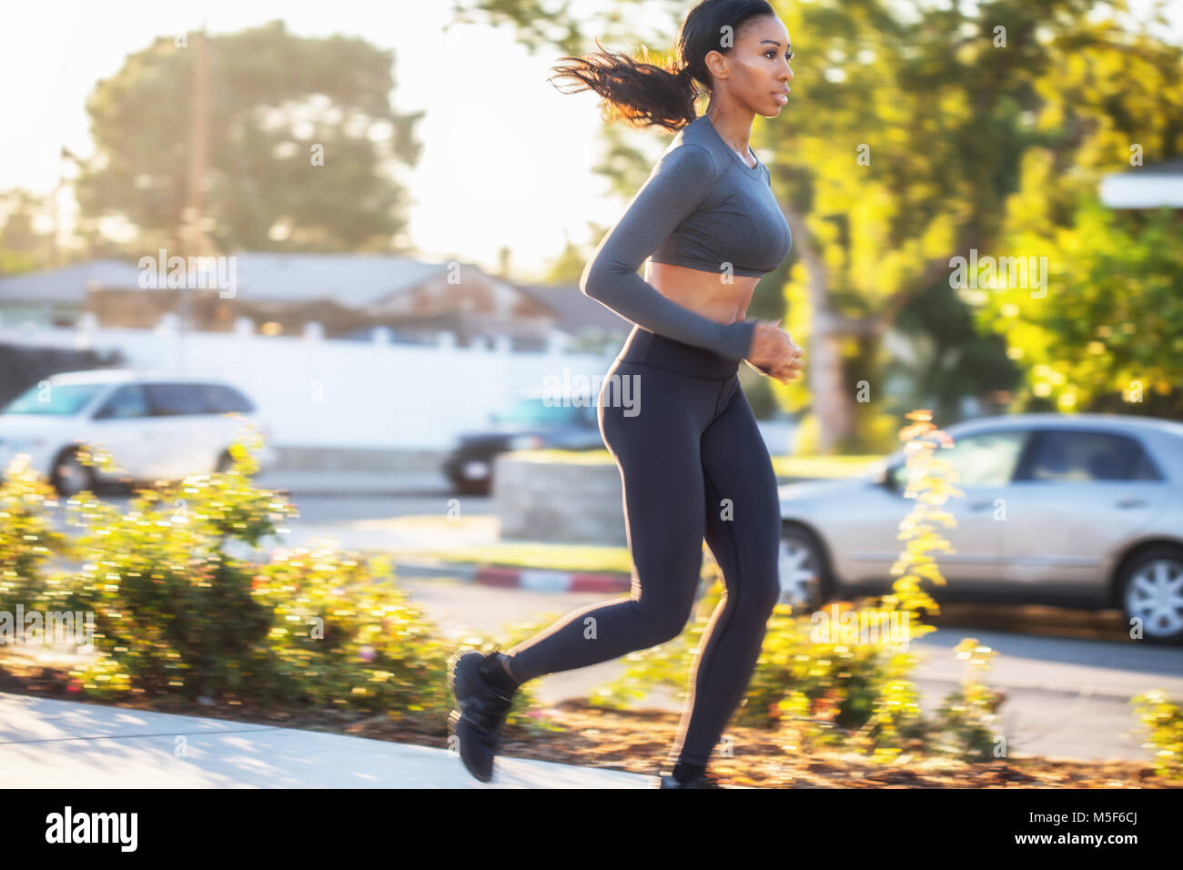 Focused young black woman running in the golden sunlight in the  - Stock Image