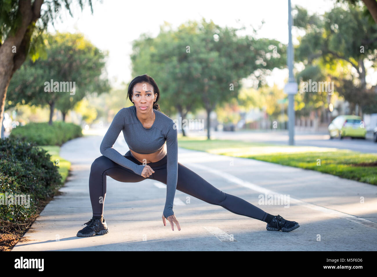 Young sporty woman in workout clothes stretching on a bike path  - Stock Image
