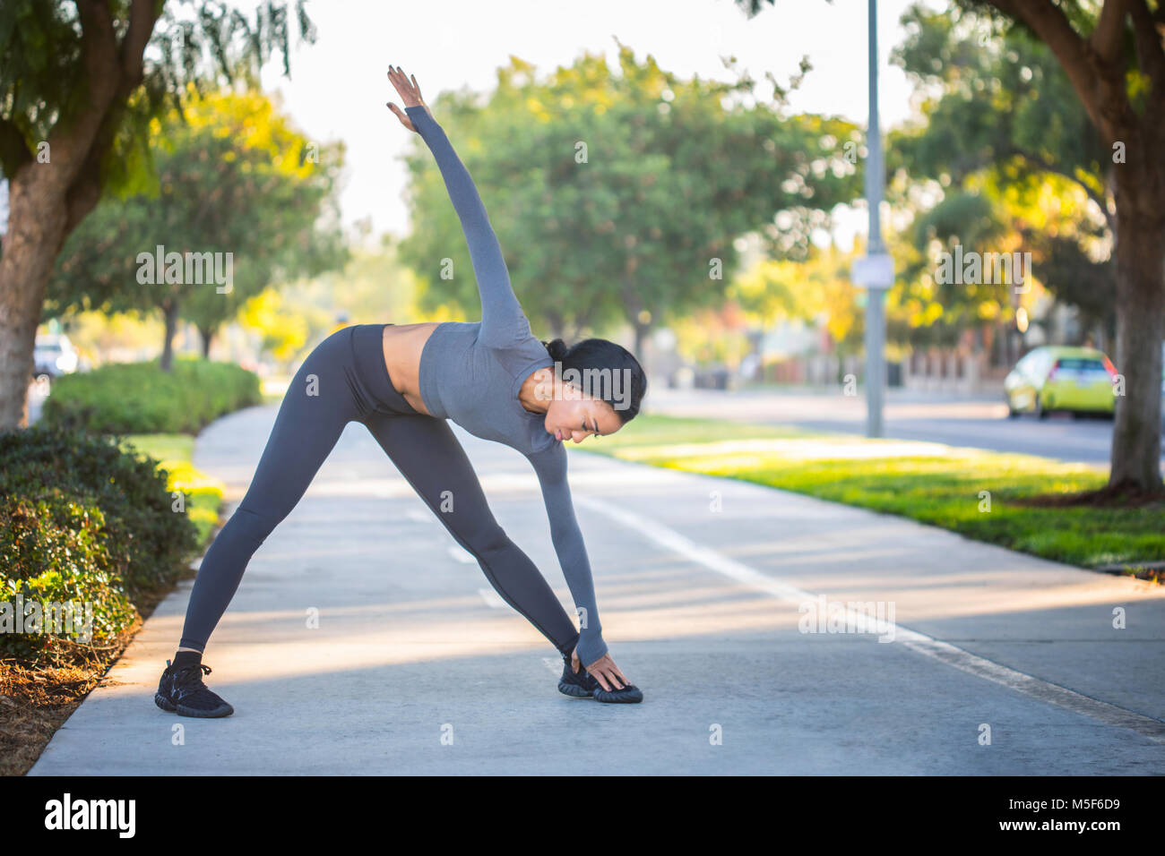 Young African American girl in workout clothes stretching on a b - Stock Image
