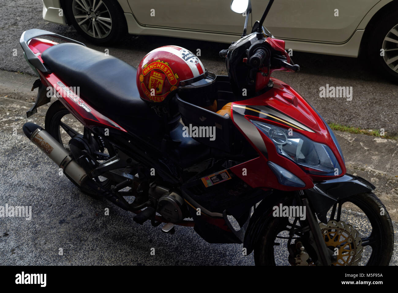 Manchester United crash helmet on a parked motorcycle, Kuching, Malaysia, Borneo Stock Photo