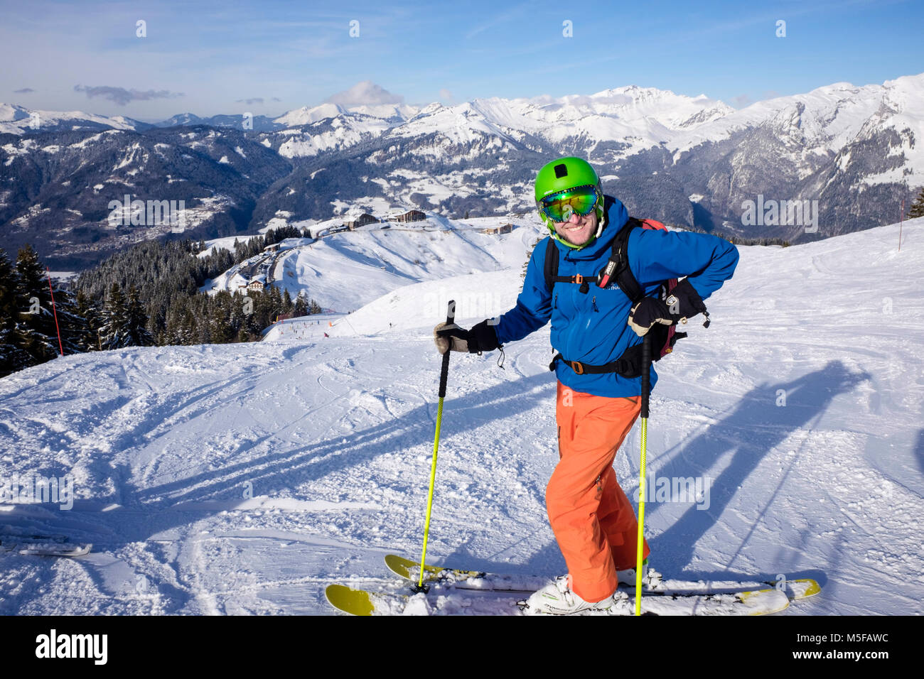 Happy male skier on skis in French Alps in winter snow skiing on red Marmotte ski slope above Samoens, Haute Savoie, - Stock Image