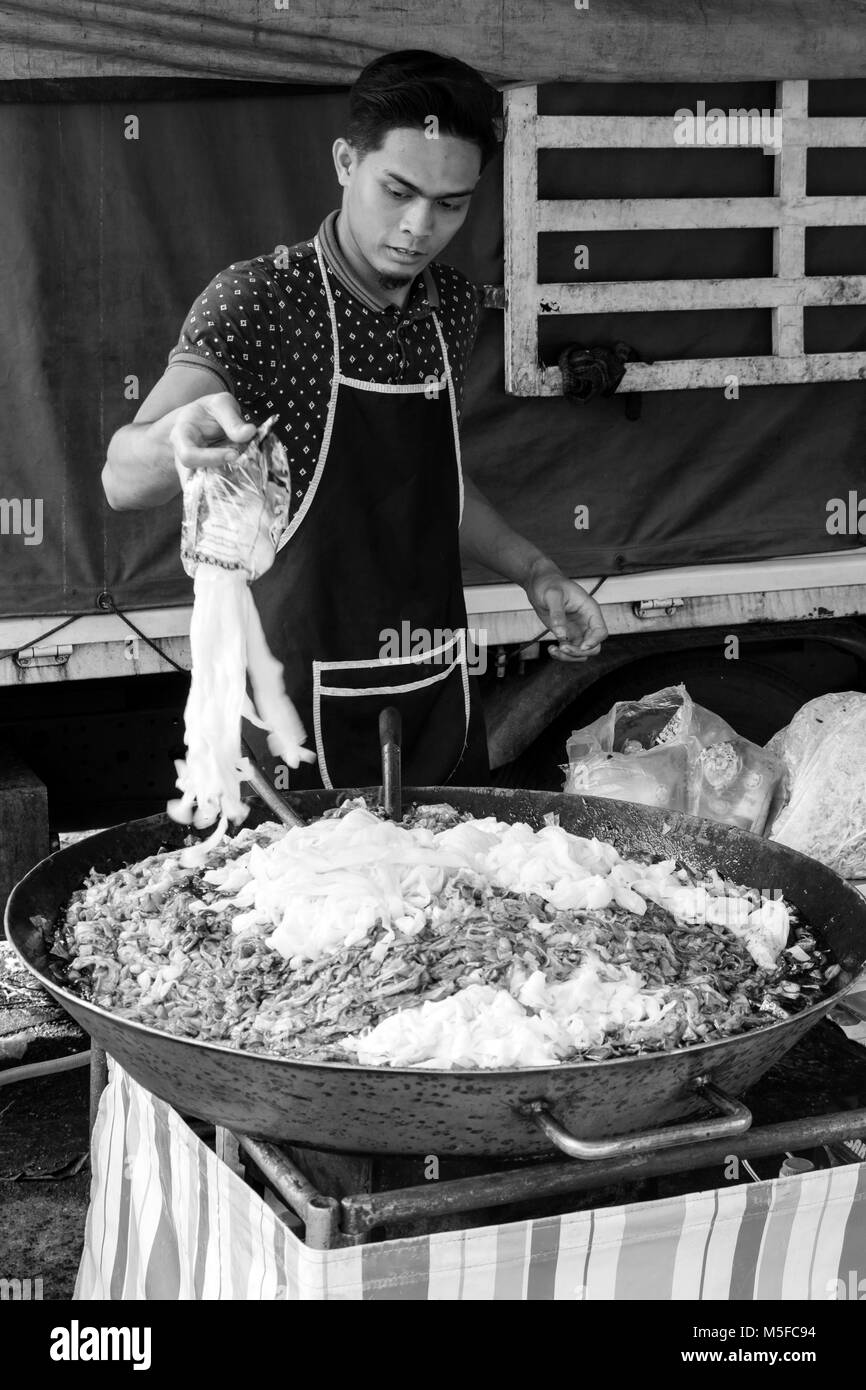 Tanah Rata, Malaysia, December 17 2017: Chef cooks fried noodles in a big pan on a market - Stock Image