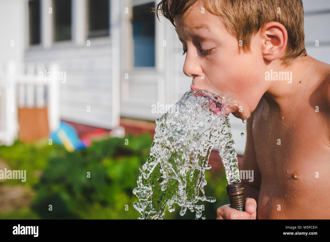 A 10-year old boy drinks water from a water hose on a sunny Summer day - Stock Image