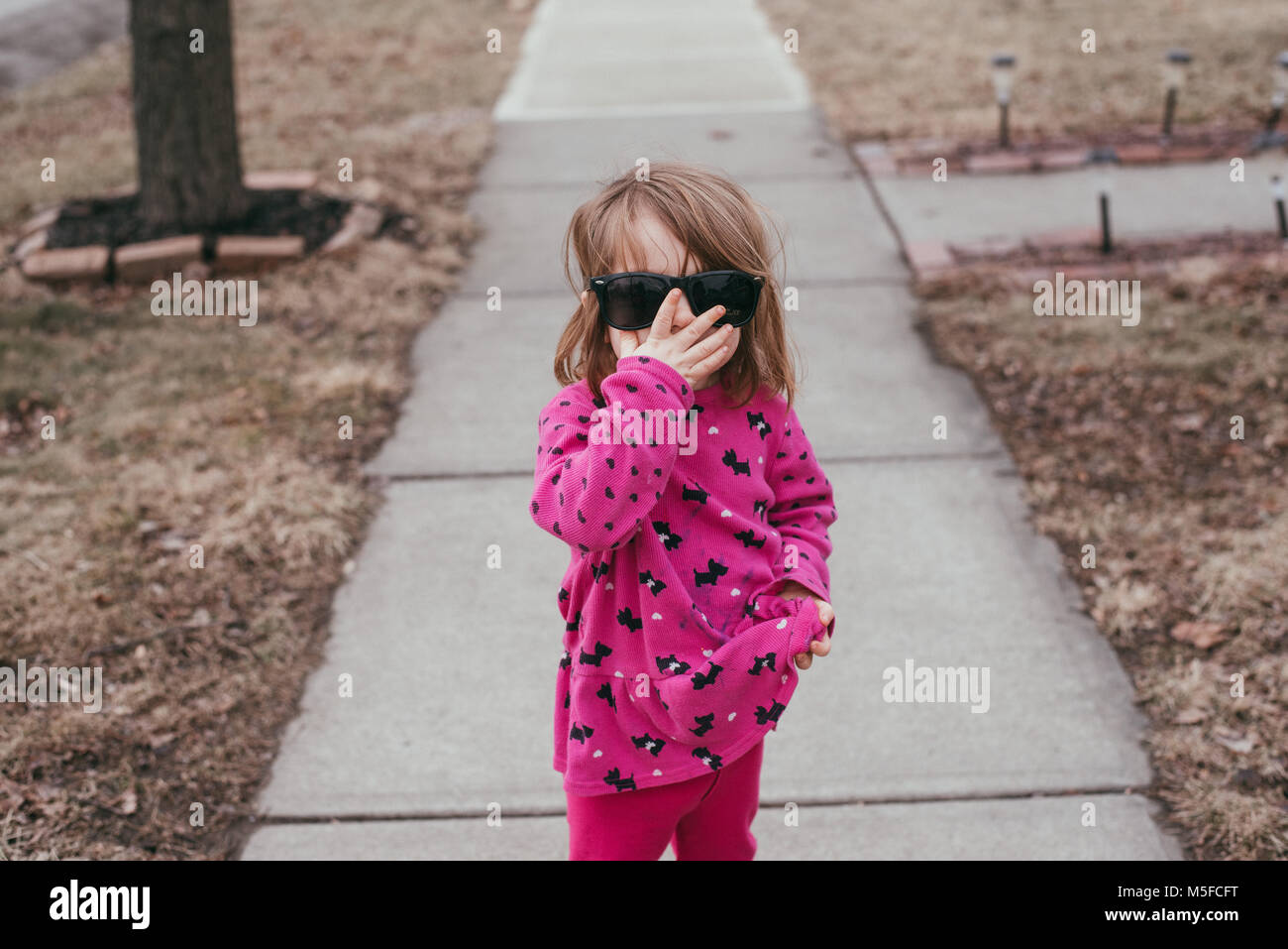 A toddler girl wearing a pink shirt and sunglasses, standing on a sidewalk on a warm, sunny day. - Stock Image