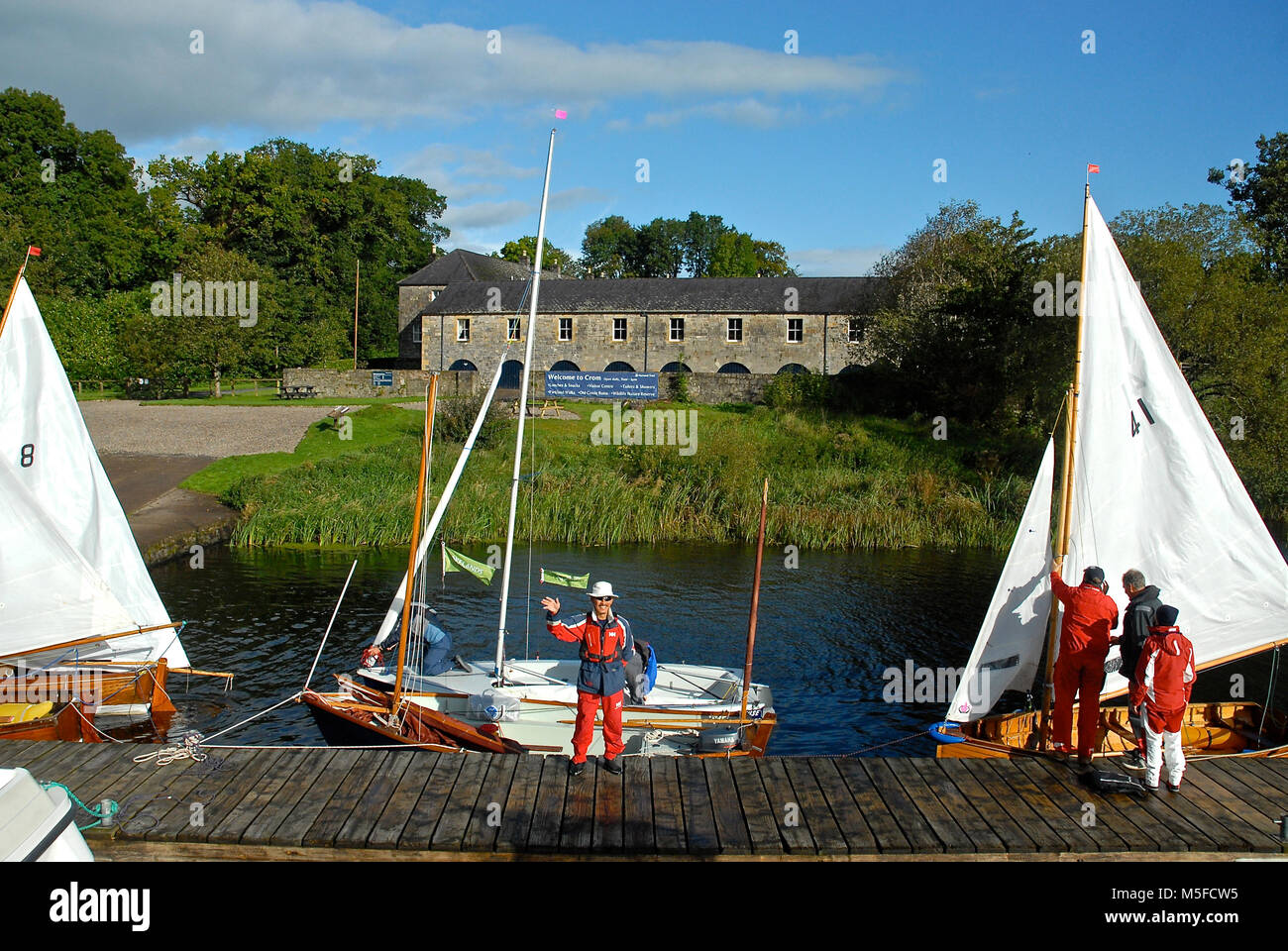 Holiday cottages at the National Trust property of Crom, Northern Ireland. A fleet of dinghies is moored at the - Stock Image