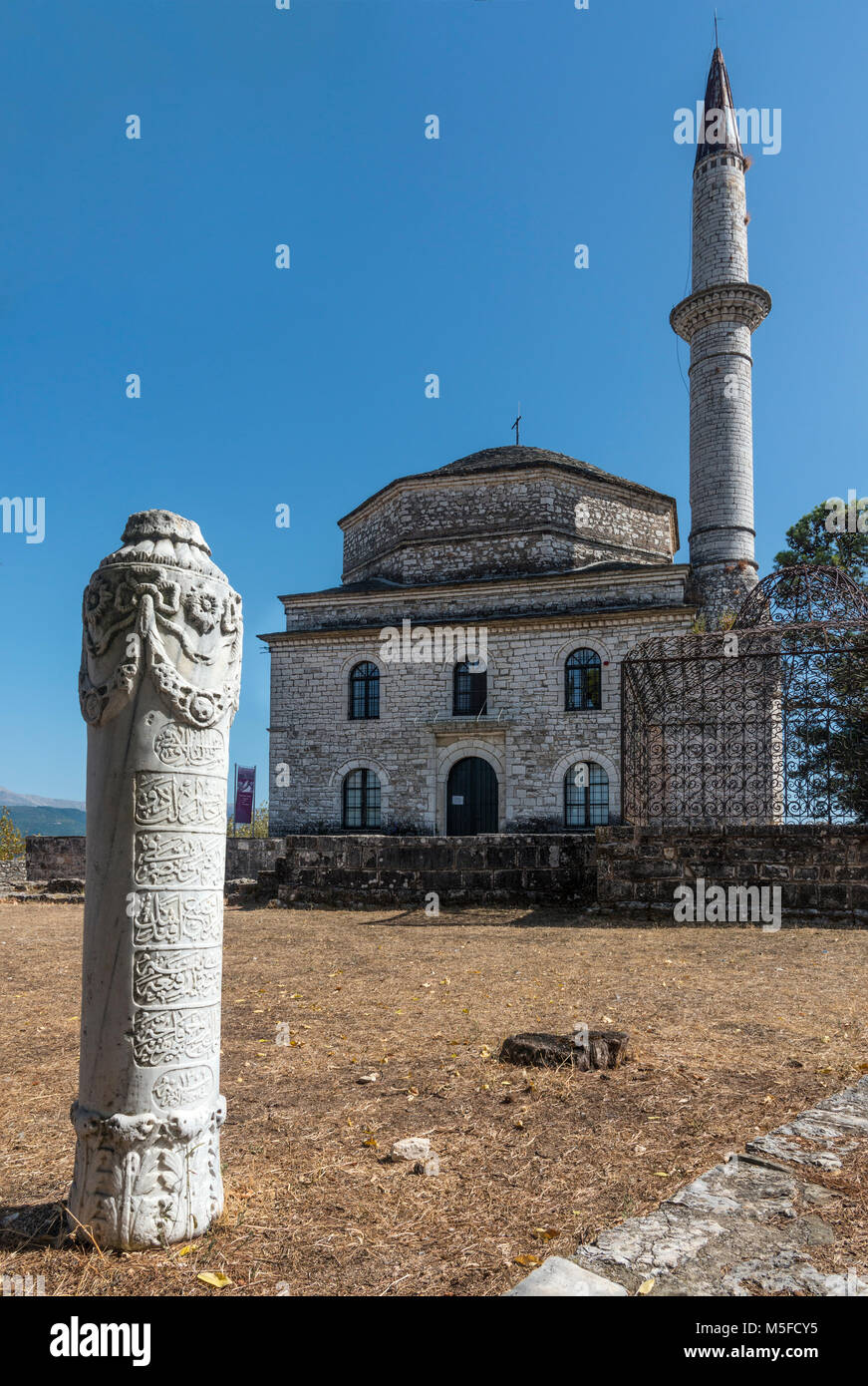 Muslim tombstone with the Fethiye mosque behind.  In the grounds of the Citadel at Ioannina, Epirus, Northern Greece. - Stock Image