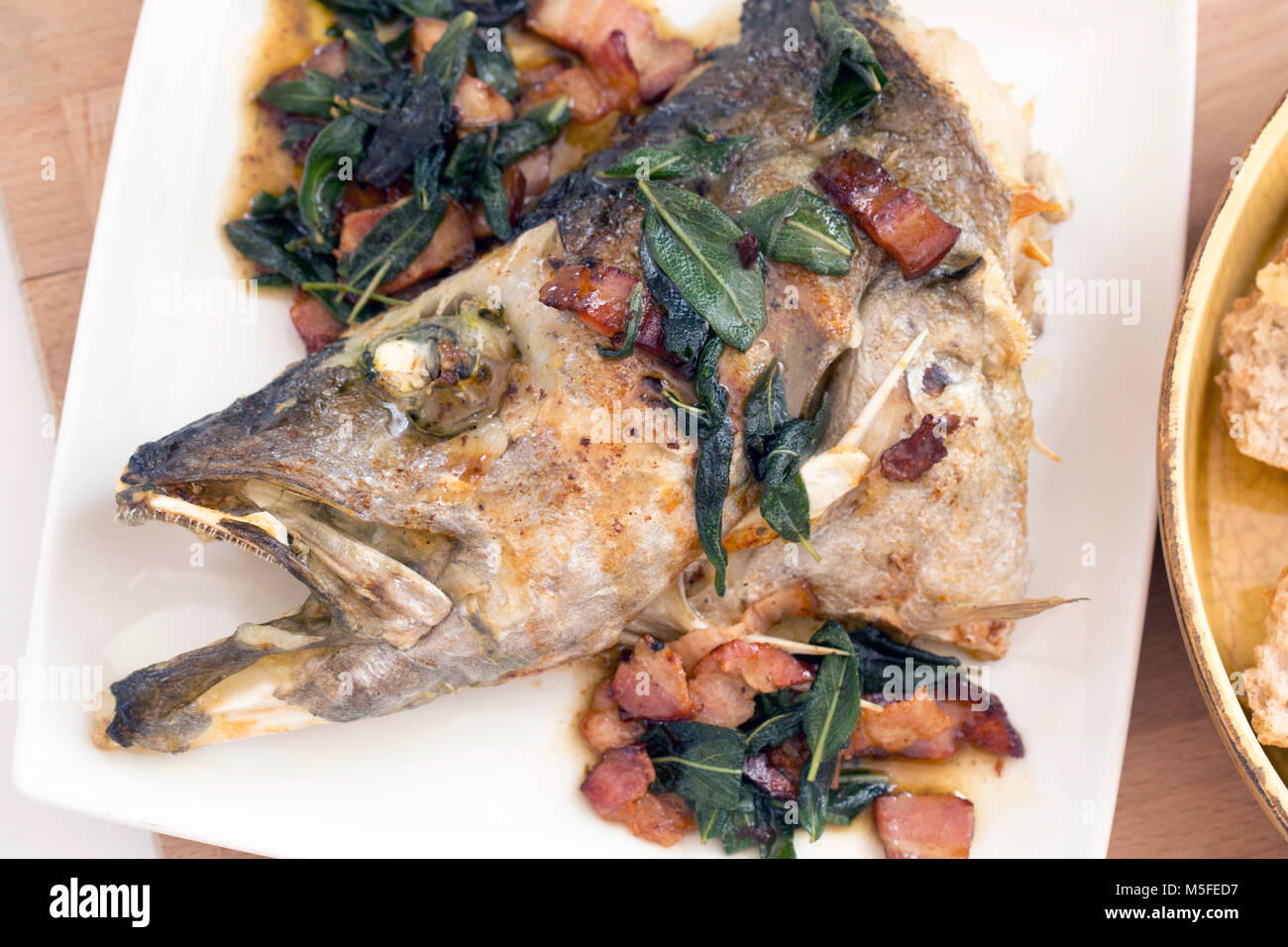 The head of a pollack caught on rod and line that has been grilled and served with fried bacon and fresh sage. Dorset - Stock Image