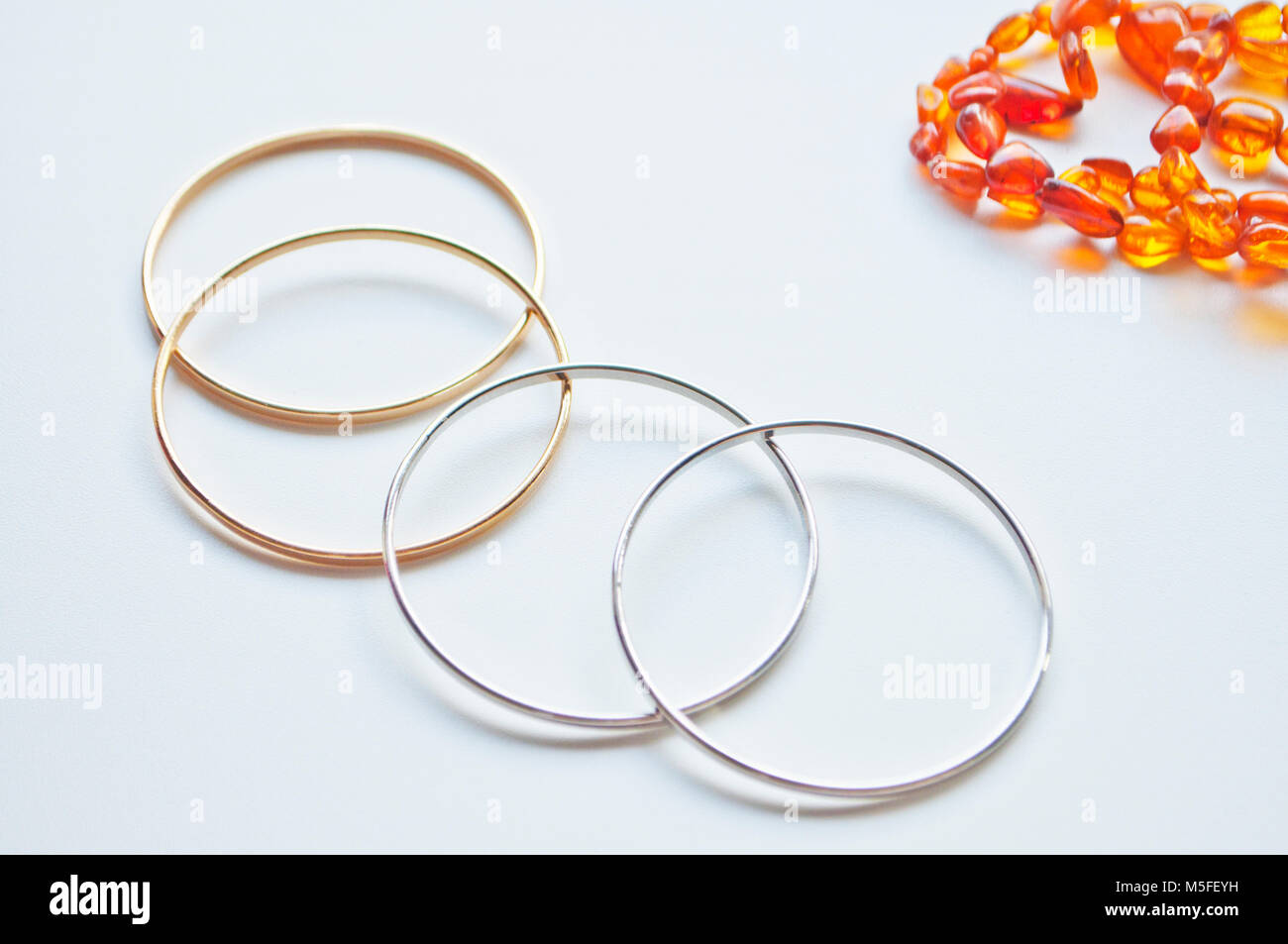 Gold ans silver bracelets isolated on a white background - Stock Image
