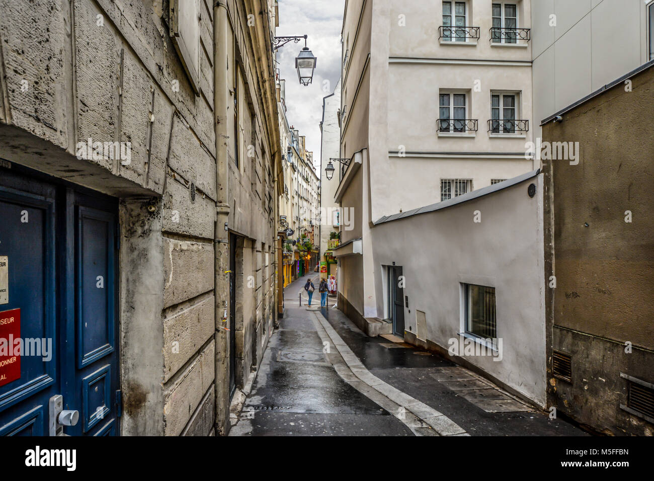 Two young ladies on an early morning walk in the Latin Quarter of Paris France pass through a narrow back alley - Stock Image