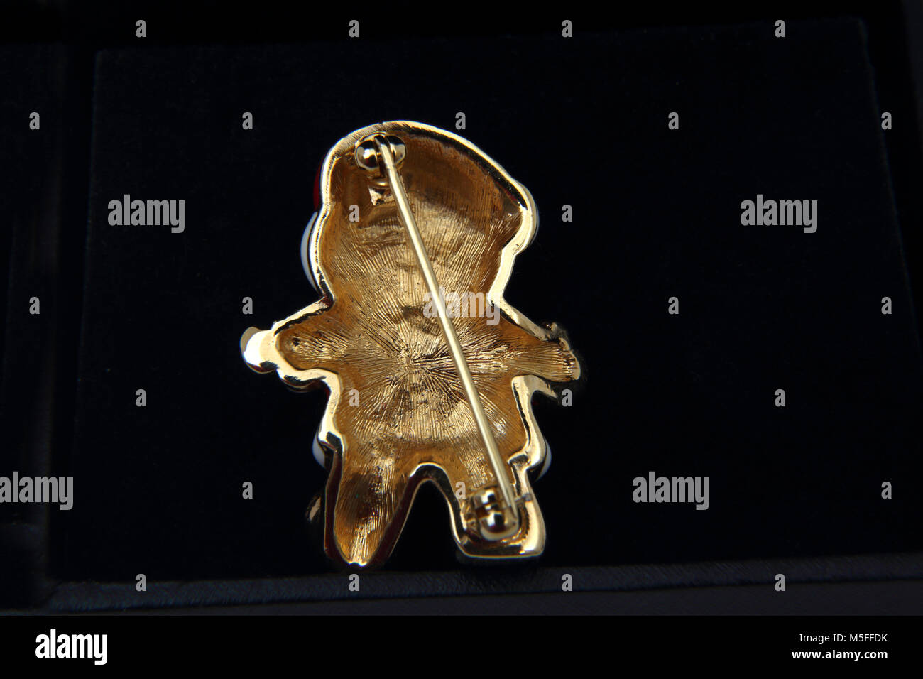 Back View Of Gold Bear Brooch With Enamel Santa Hat And Suit - Stock Image