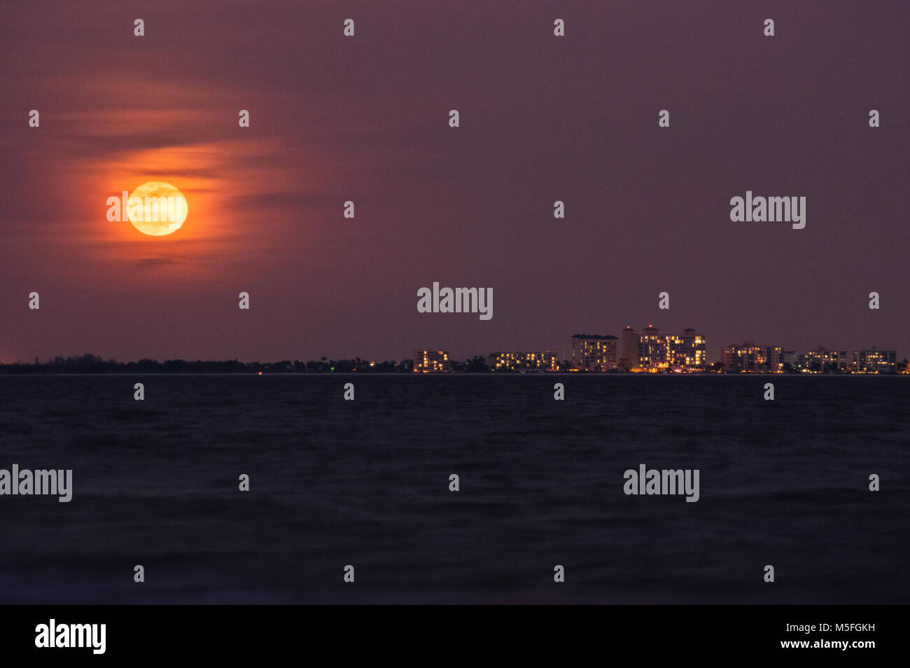 A full red moon rises above the large condos that line the horizon's edge across Fort Myers Beach in Florida. - Stock Image