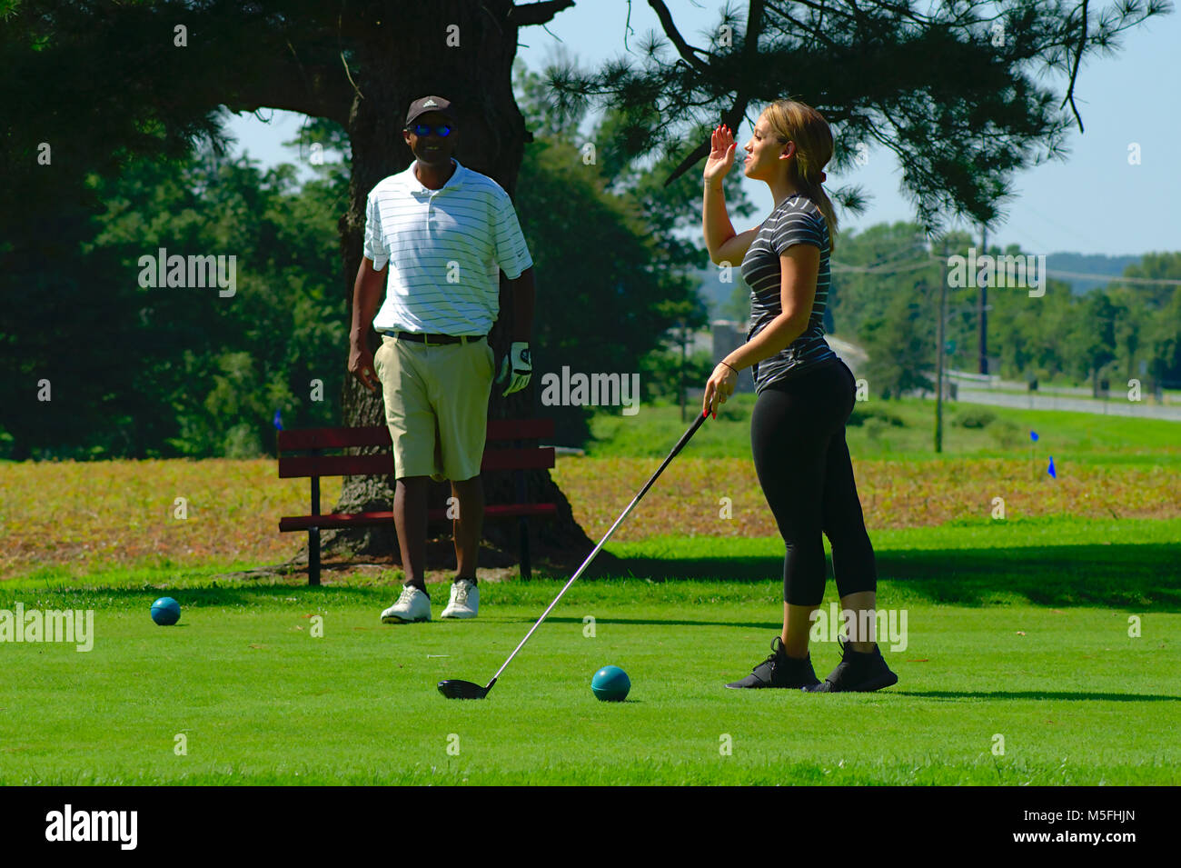 Golf twosome teeing off - Stock Image