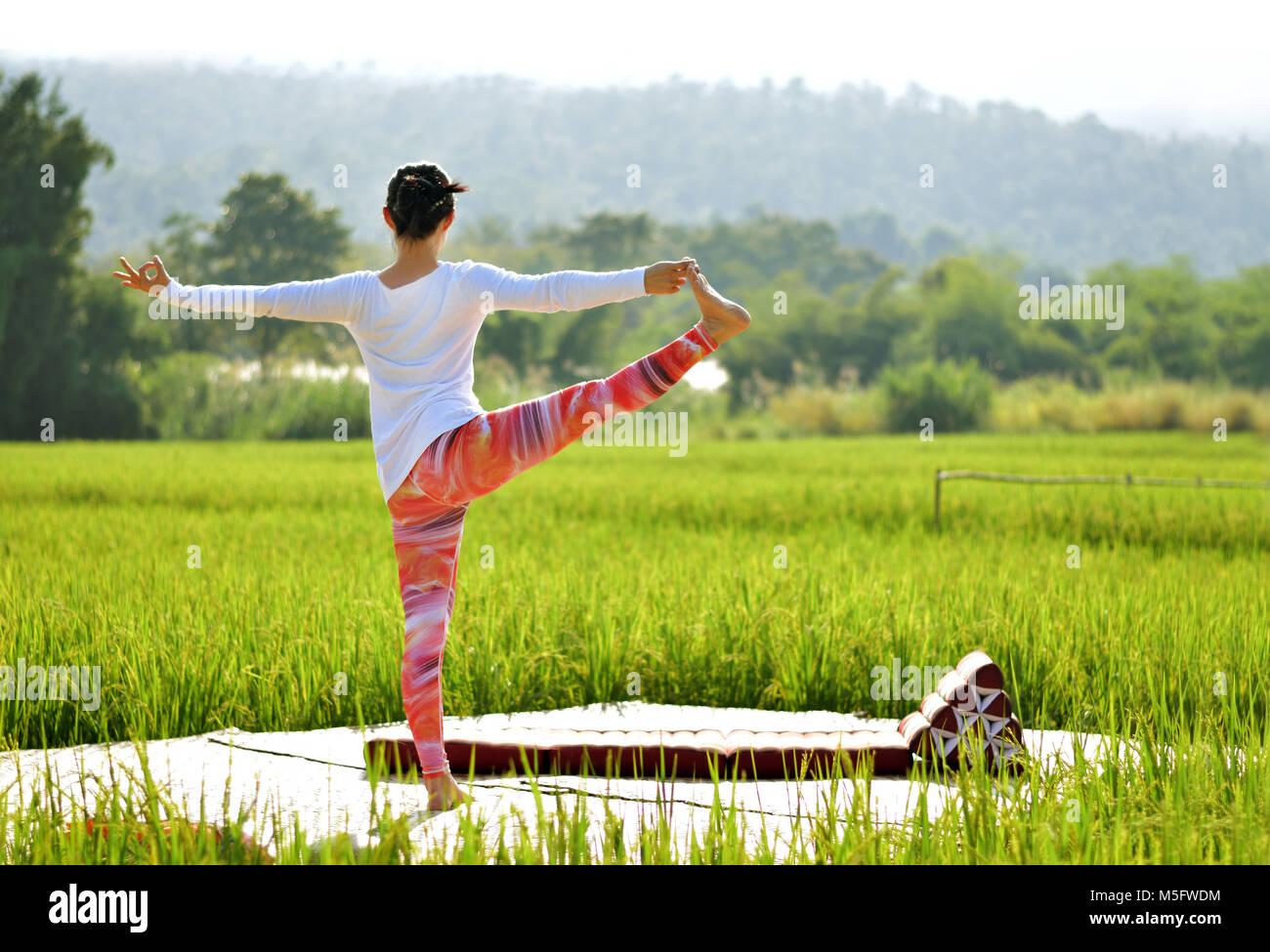 Soft focus image of woman do variation of utthita hasta padangusthasana yoga pose on terrace in green rice field, - Stock Image