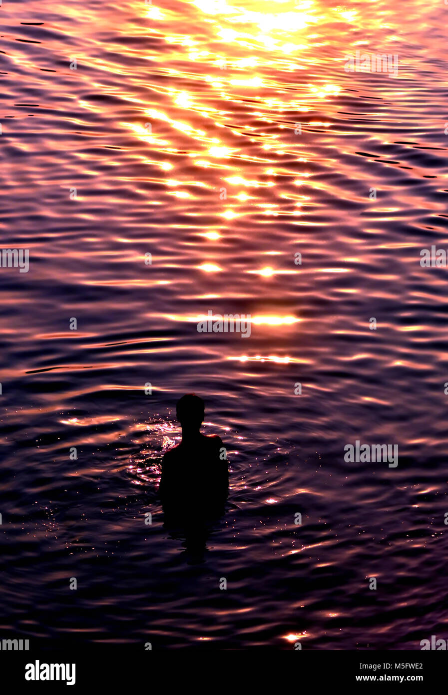 Summer activity, a blur abstract silhouette photo of a man enjoy his activity alone in a water during a hot weather - Stock Image