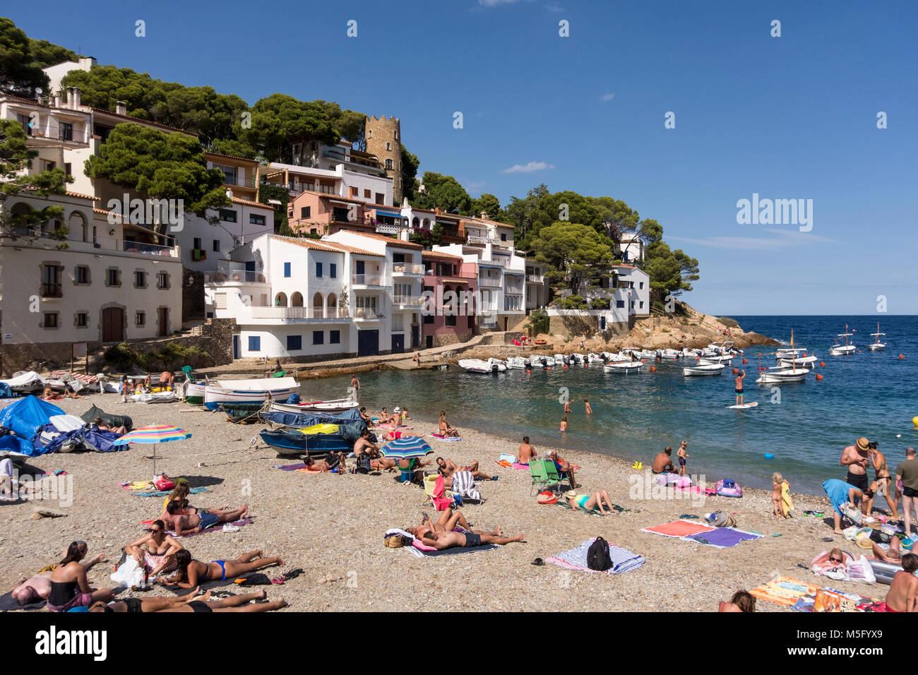 Holidaymakers on the beach at Cove of Sa Tuna, Begur, Baix d'Emporda, Costa Brava, Catalonia, Spain - Stock Image