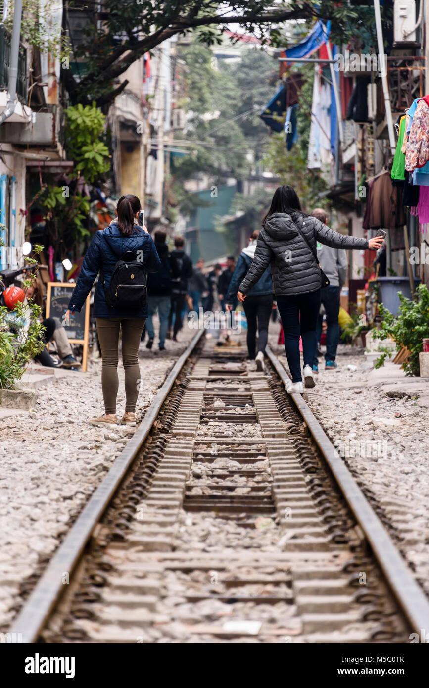 "Chinese tourists walk along ""Hanoi Train Street"", a narrow street in the centre of Hanoi with live railway tracks Stock Photo"