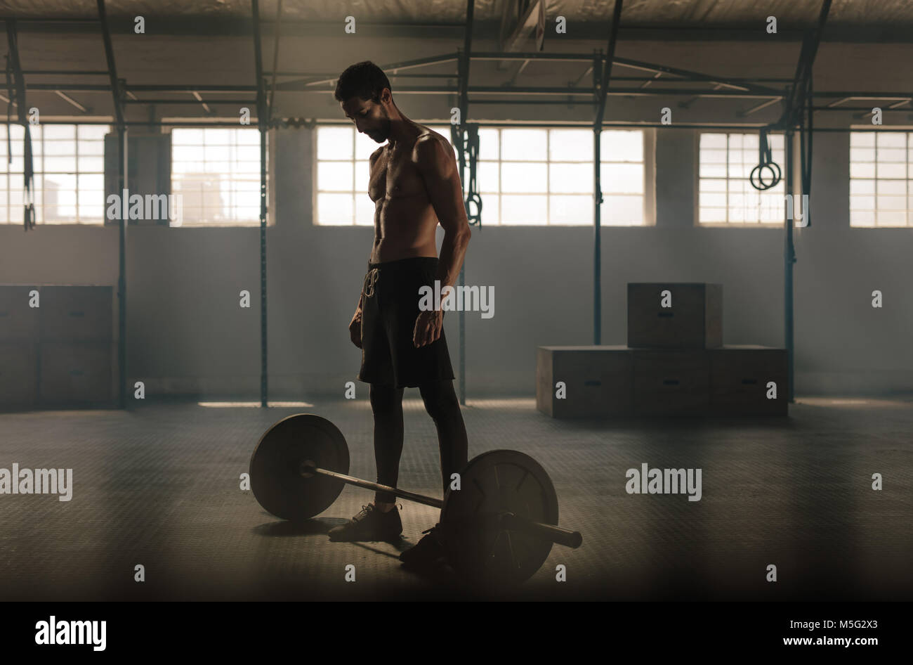 Man exercising with barbell at gym. Man standing with heavy weights barbell on gym floor. - Stock Image