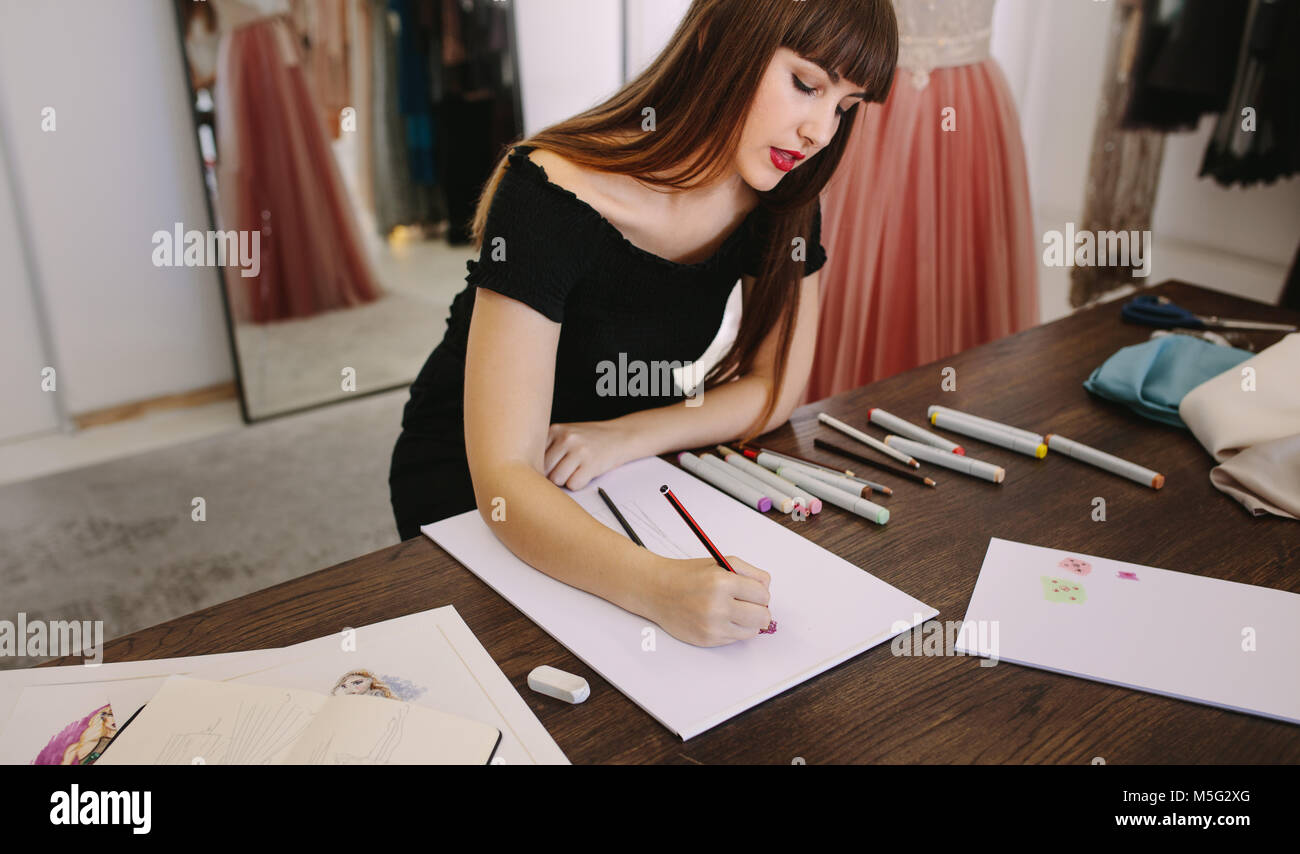 Female fashion entrepreneur sketching a design sitting at her table. Fashion designer making a drawing in her cloth - Stock Image