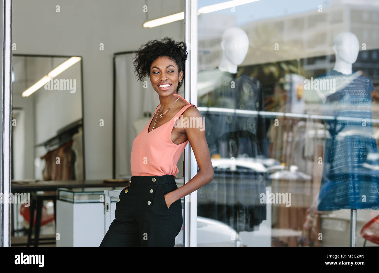 Smiling dress designer in her cloth shop with designer clothes on display. Woman entrepreneur standing at the entrance - Stock Image