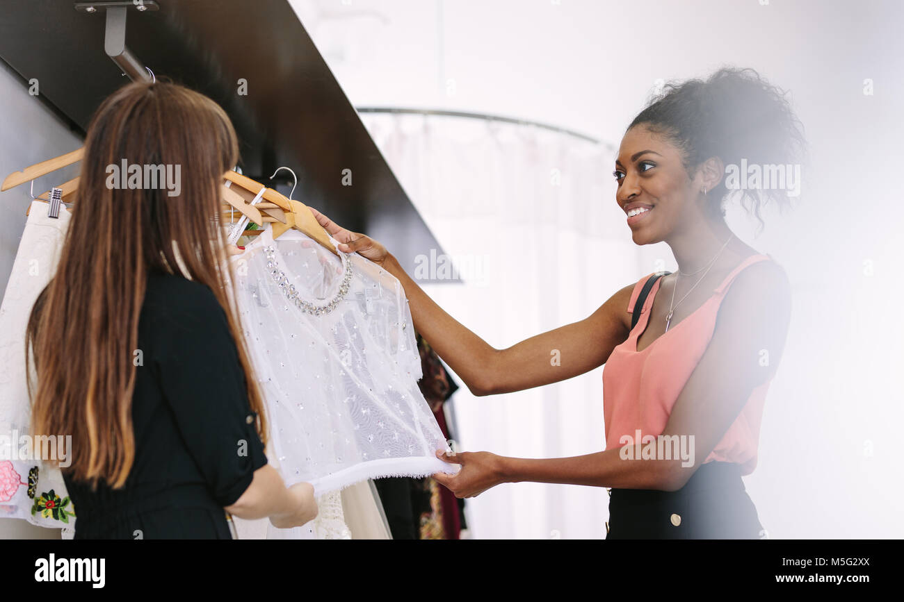 Customer having a look at dresses in a boutique. Woman entrepreneur showing designer clothes to a customer. - Stock Image
