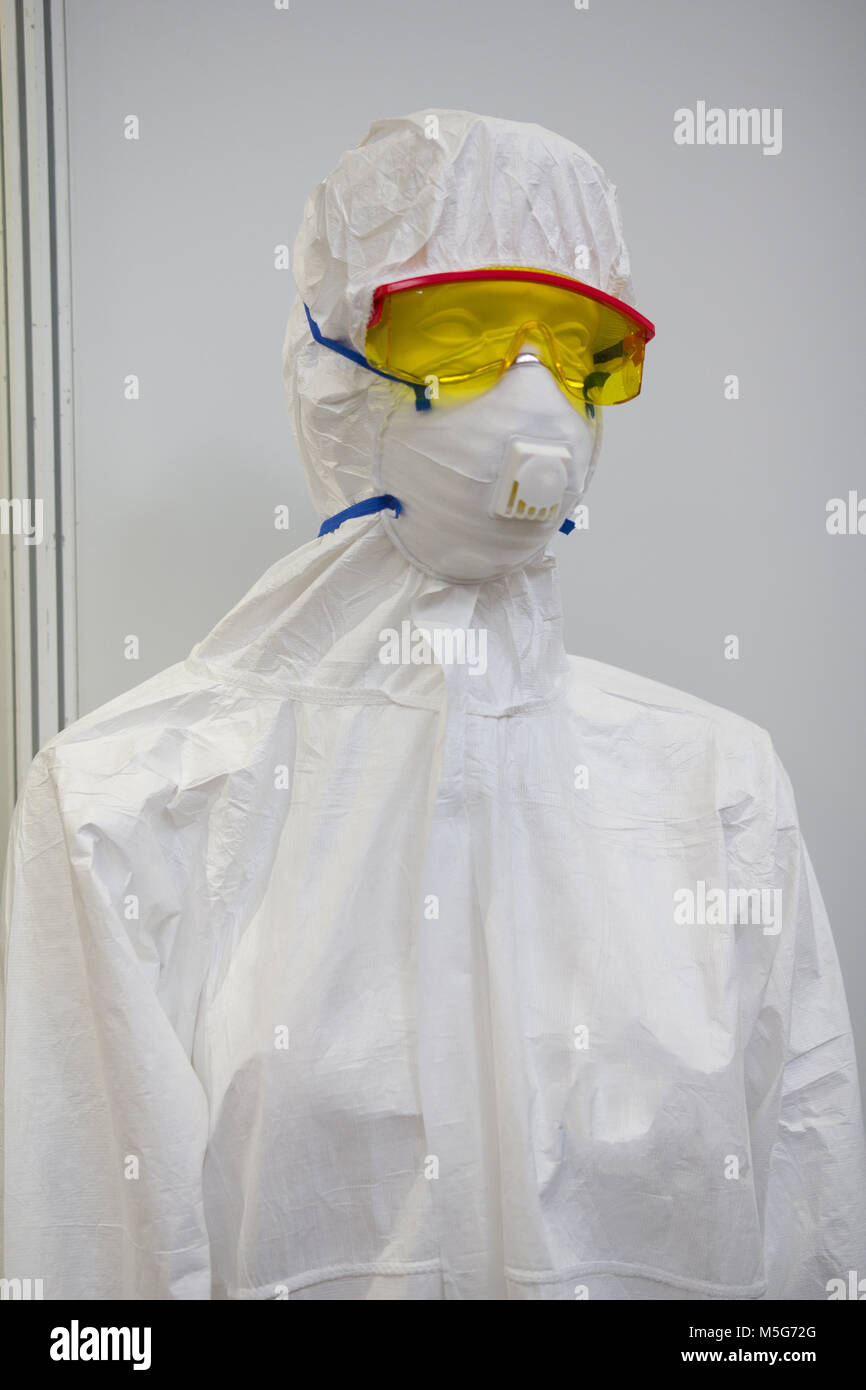 Mannequin in white protective clothing, respirator and plastic glasses - Stock Image