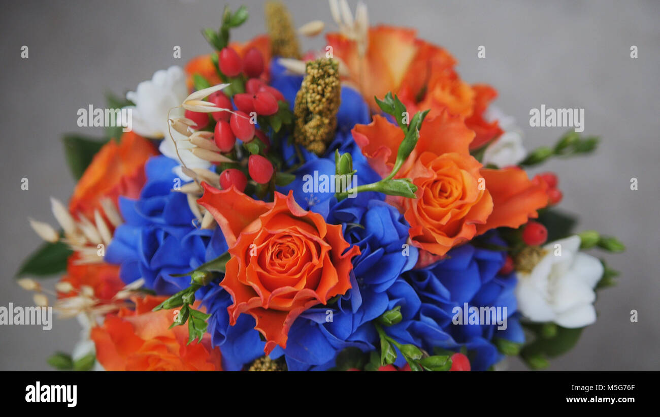 Wedding bouquet on a grey surface - red roses and blue blossoms - Stock Image