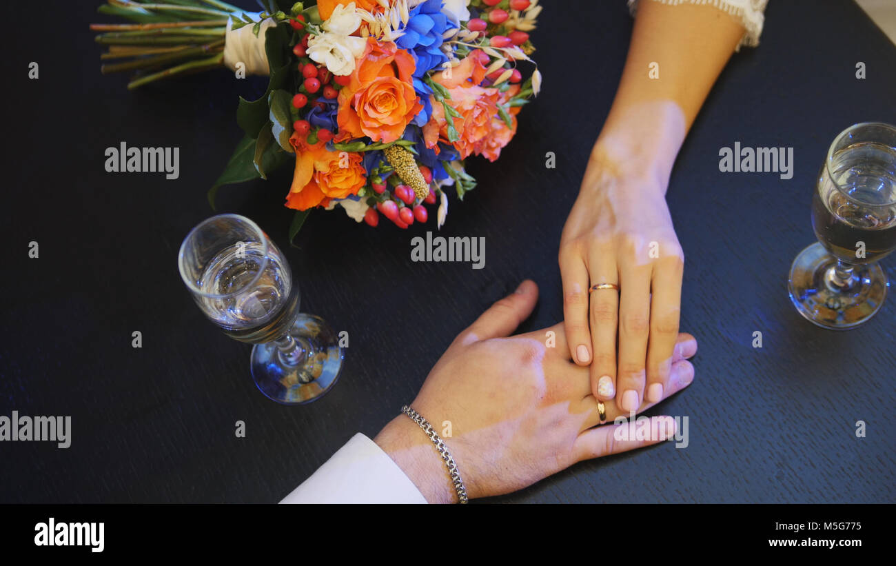 Man's and woman' hands on the table in cafe - wedding concept - Stock Image