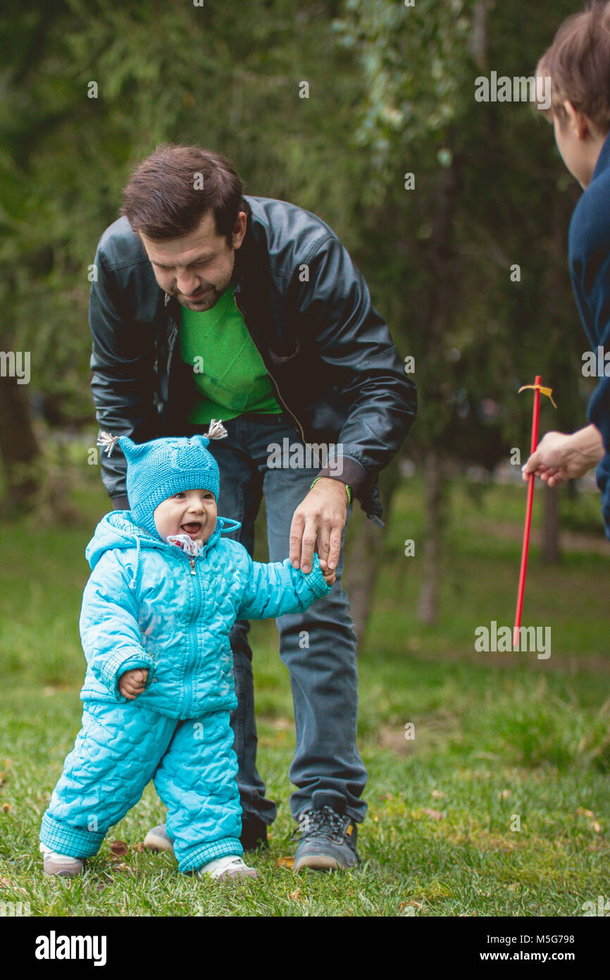 Happy family walking in autumn park: mother, father and his little son - learn to stroll independently - Stock Image