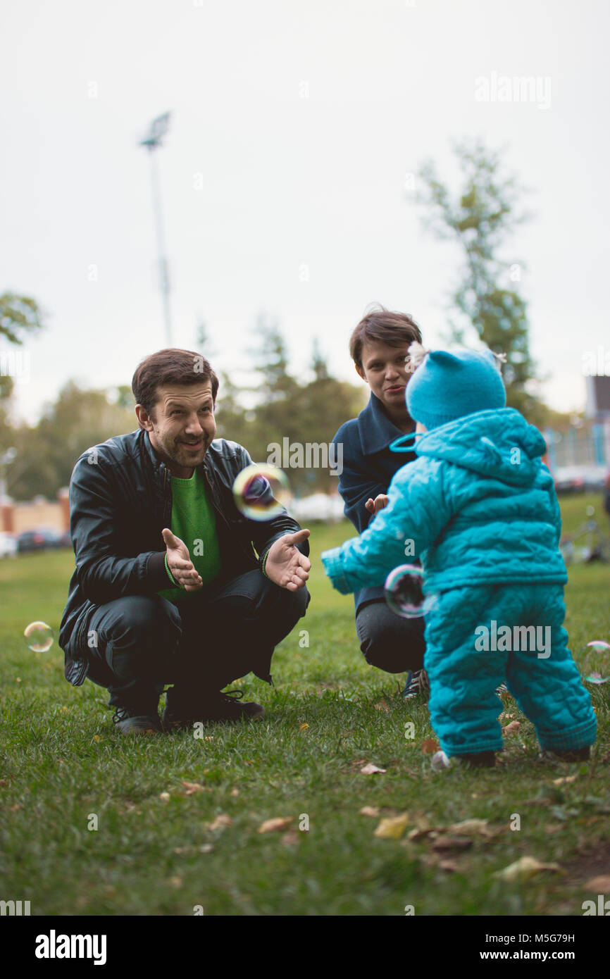 Happy family walking in autumn park: mother, father and their little son - learn to stroll independently - Stock Image