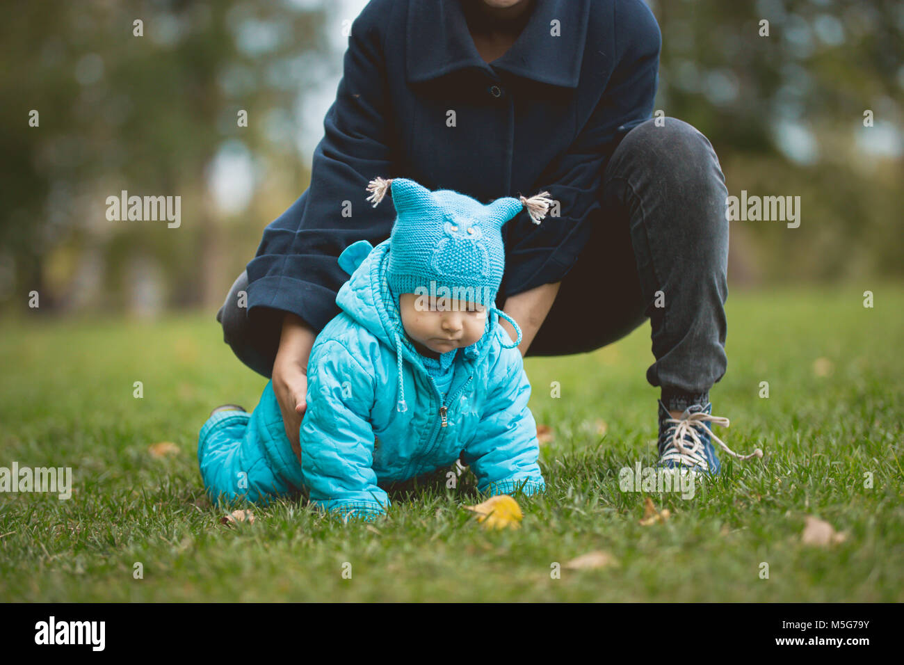 Happy family walking in autumn park: boy crawling on the grass with mother - Stock Image